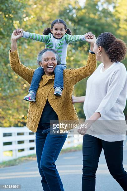 three generations of women walking together - black granny stock photos and pictures