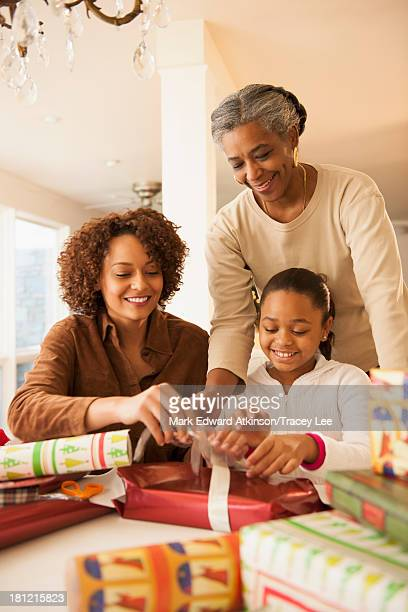 Three generations of women wrapping Christmas presents