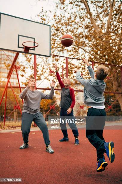 three generations playing basketball - vertical stock pictures, royalty-free photos & images