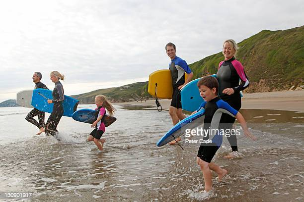three generations running into sea with boards