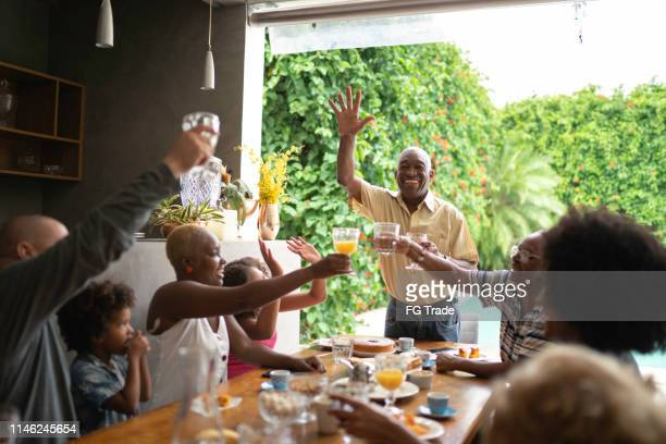 three generations toasting in breakfast while senior man makes a speech - gratitude stock pictures, royalty-free photos & images