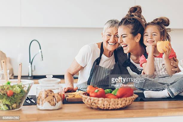 three generations women laughing in the kitchen - healthy lifestyle stock pictures, royalty-free photos & images