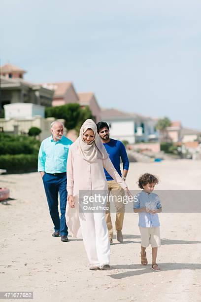 Three Genration Arabic family walking on the beach