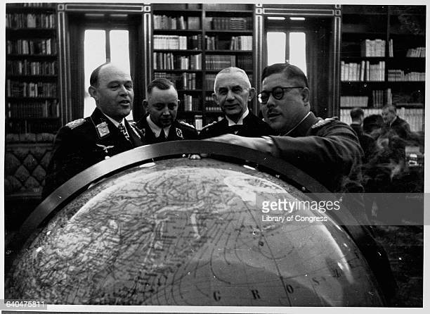 Three German generals and a Japanese general examine a globe in March 1941
