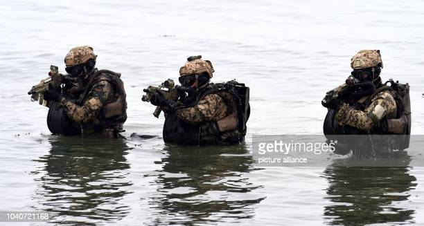 Three German Navy frogmen wade through the water as they arrive on the beach during a military presentation in Eckernfoerde Germany 5 April 2014 The...