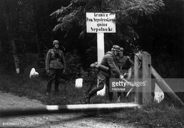 Three German soldiers chop down a gate demarcating the border between Germany and Poland with a ax on the day Nazi Germany invaded Poland September 1...