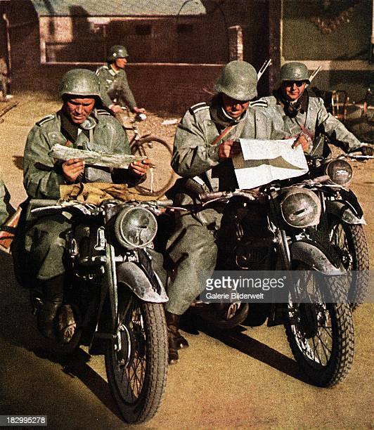 Three German soldiers of the Wehrmacht on motorcycles are studying road maps France circa 1940 One is on a bicycle Motorcycle units were basically...