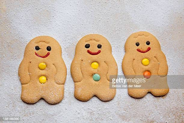 three gingerman cookies in a row on icing sugar. - gingerbread men stock pictures, royalty-free photos & images