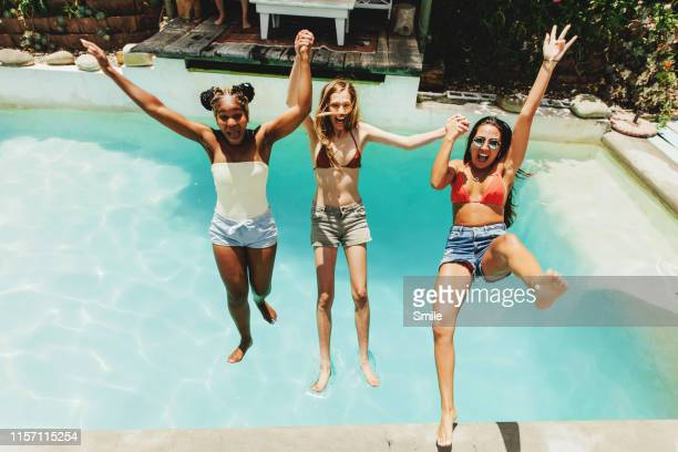 three girlfriends falling backwards into swimming pool - female friendship stock pictures, royalty-free photos & images