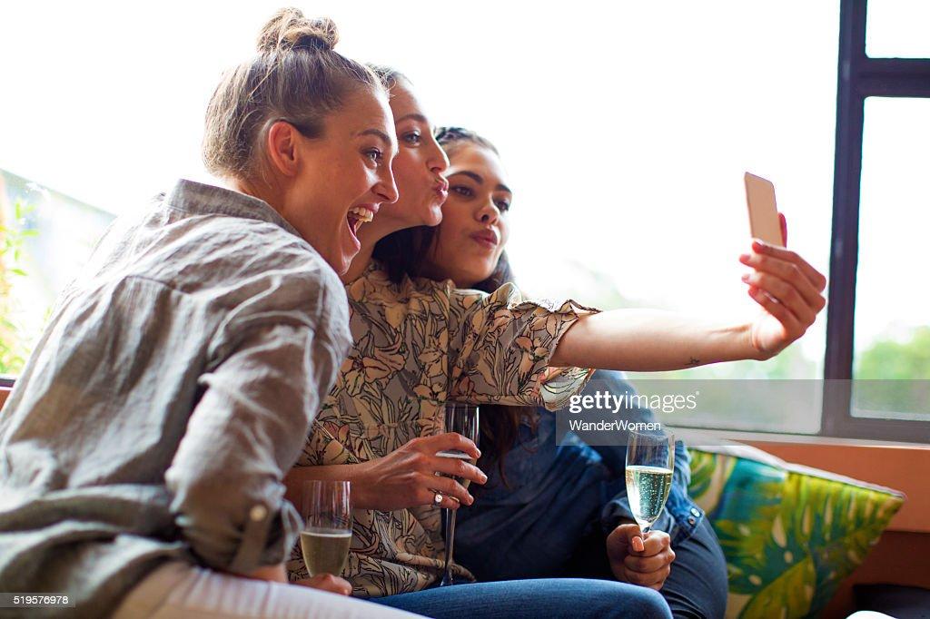 Three girlfriends having champagne taking selfie : Stock Photo