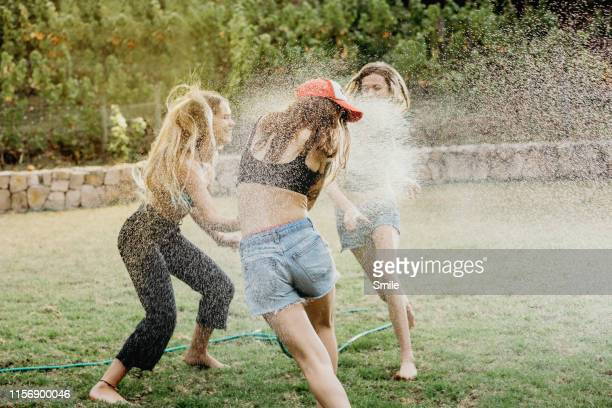 three girlfriends playing with sprinkler on lawn - ducking stock pictures, royalty-free photos & images