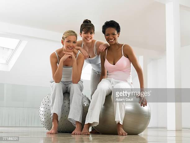 Three girlfriends with pilates balls