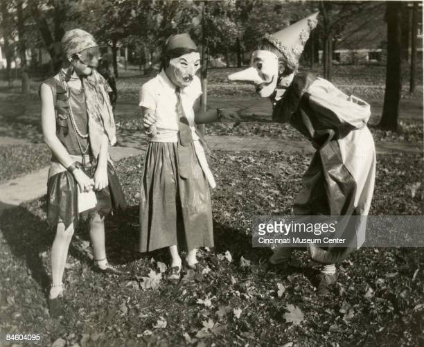Three girls amuse each other with their masked costumes as they prepare for Halloween festivities in the College Hill neighborhood of Cincinnati,...