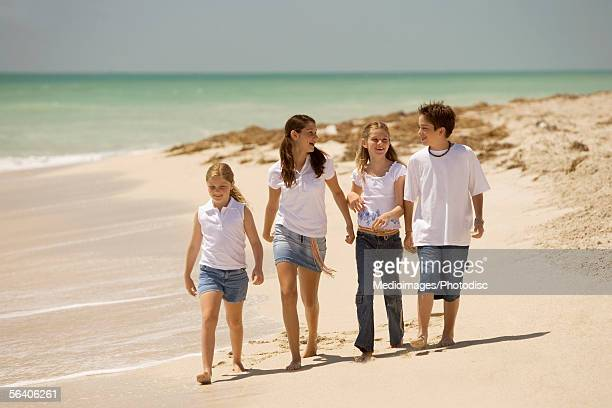 three girls and a boy walking on the beach - 13 years old girl in jeans stock photos and pictures