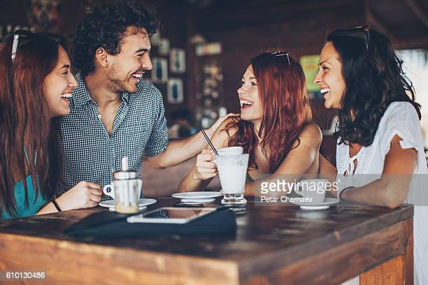 Three girls and one man talking in cafe