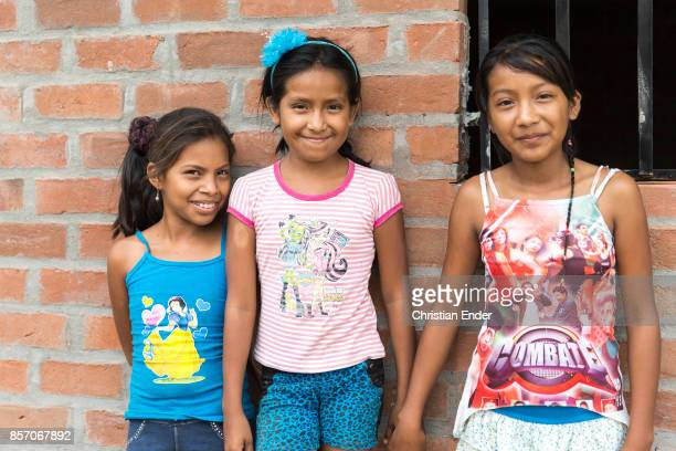 Three girls are holding hands and smiling into the camera standing in front of a brick building wearning shirts with colorful prints near Sullana peru