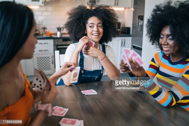 three girls at home playing cards - board game stock pictures, royalty-free photos & images