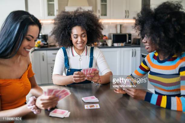 three girls at home playing cards - game night leisure activity stock pictures, royalty-free photos & images