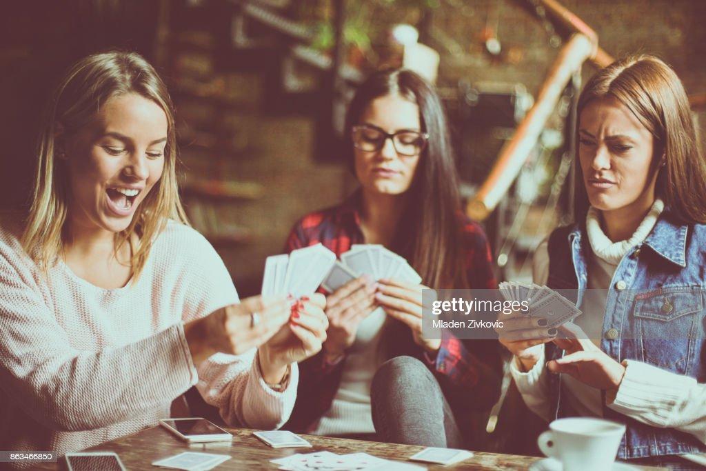 Três meninas em casa jogando cartas. : Foto de stock