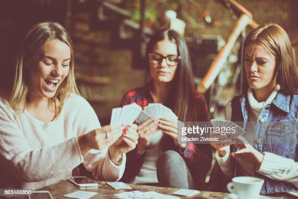 three girls at home playing cards. - poker card game stock photos and pictures