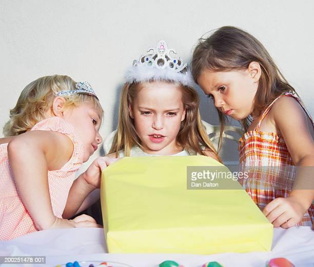 Three girls (5-8) at table opening birthday present
