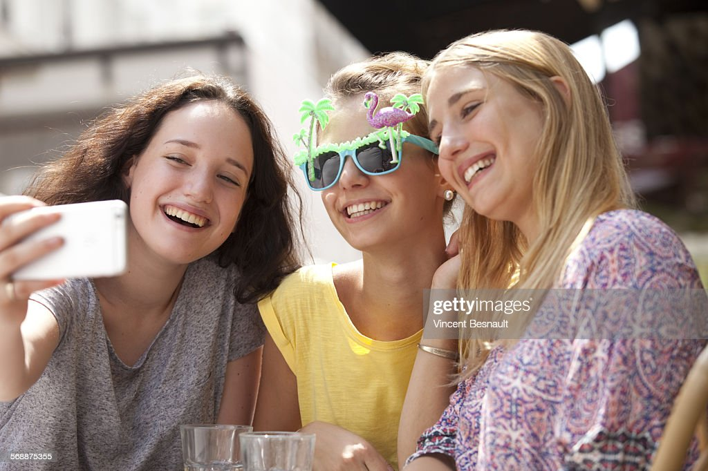 Three girls doing a selfie in the street : Stock Photo