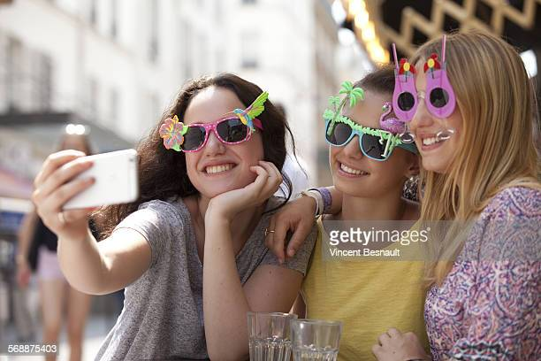 Three girls doing a selfie in the street