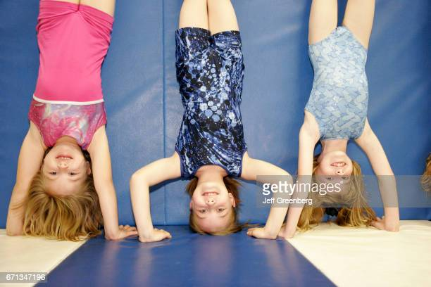 Three girls doing handstands in a gymnastics class at Westgate Park Recreation Center