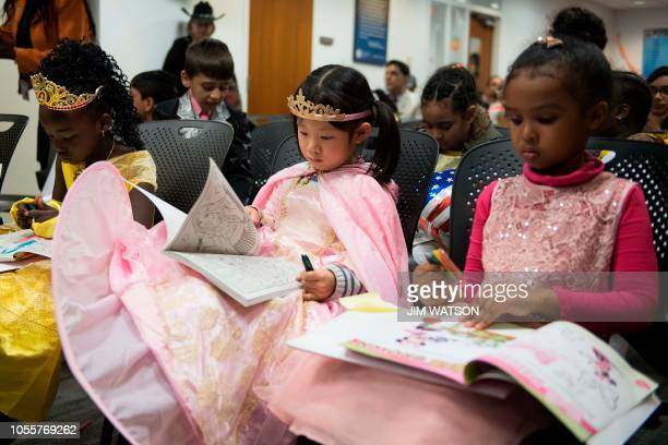 Three girls dressed as princesses wait and color as part of thirtyfive children from 22 countries who celebrated their US citizenship during a...
