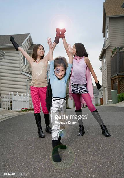 three girls (6-11) dressed as superheros, arms raised - little girls dressed up wearing pantyhose stock photos and pictures
