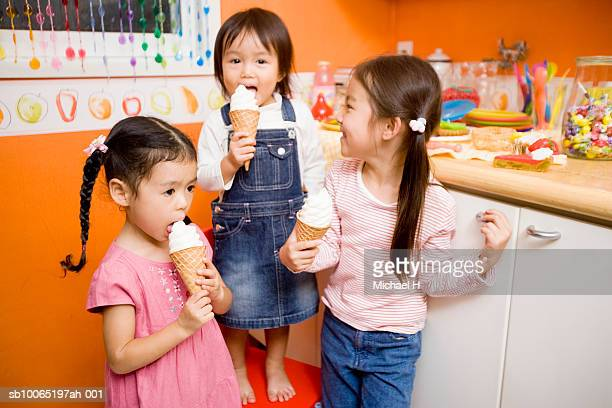 Three girls (2-5) eating ice cream in kitchen