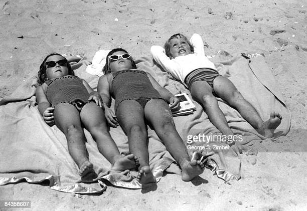 Three girls enjoy the sun while lying down on a blanket on an unidentified beach in New York 1959