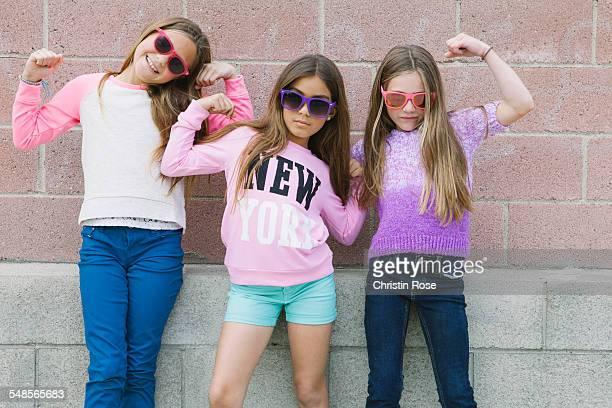 Three girls flexing muscles