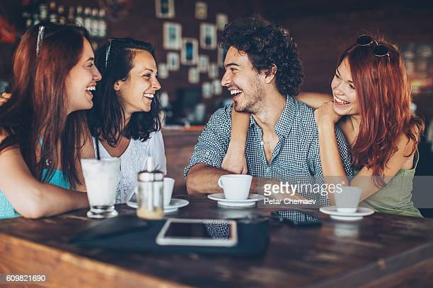 Three girls flirting with a man in cafe