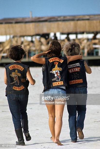 Three girls from the Bandidos gang shot from behind walking on the beach wearing their biker jackets Texas September 1969