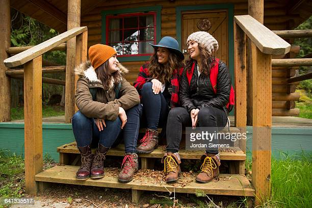 Three girls hangin out on a cabin porch.