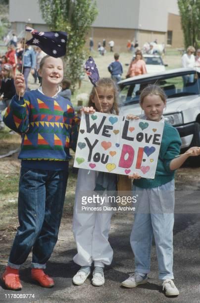 Three girls holding a sign reading 'We Love You Di' wait to meet Diana Princess of Wales in Macedon Australia November 1985