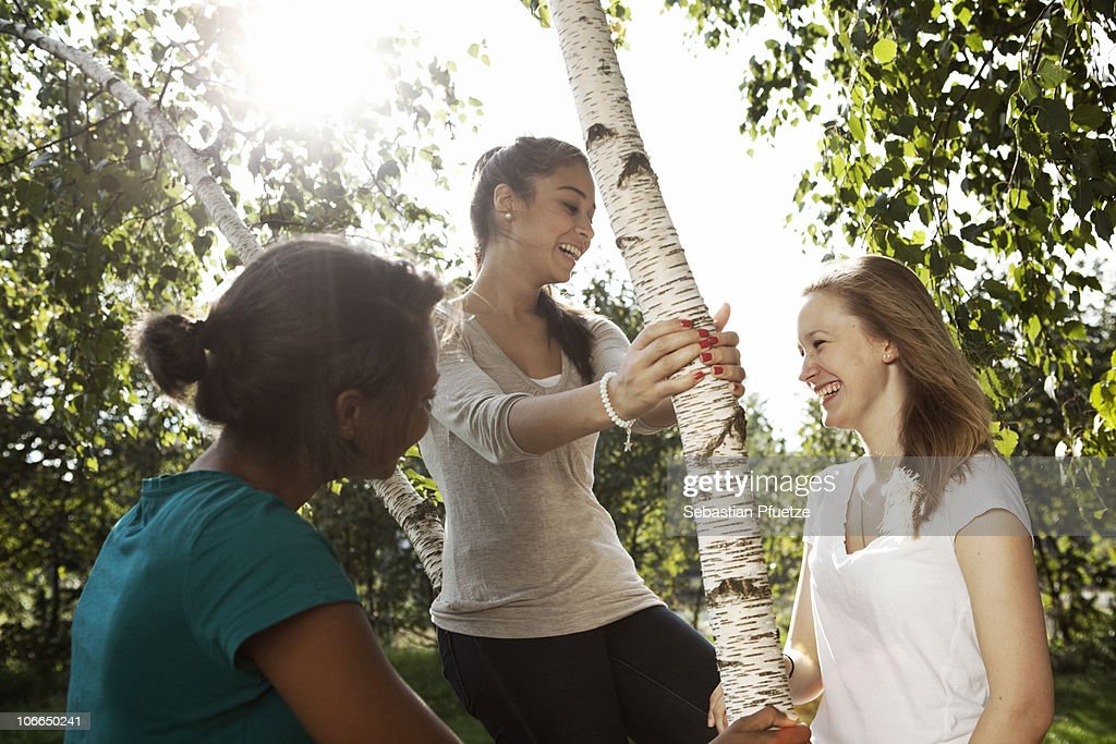 Three girls in a park laughing : Stock Photo