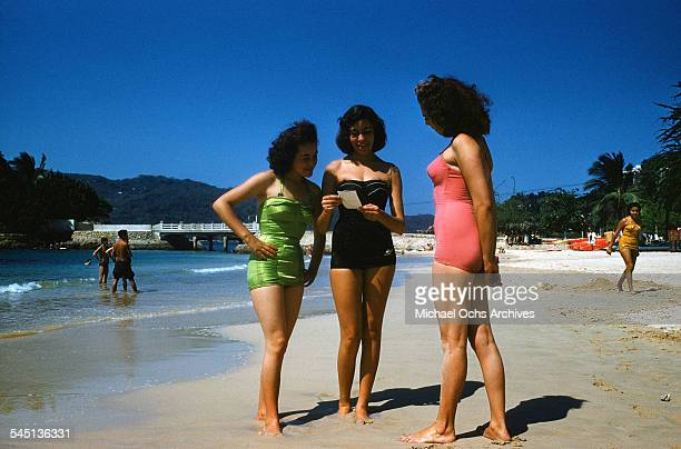 Three girls in bathing suits stand on a beach in Acapulco Mexico