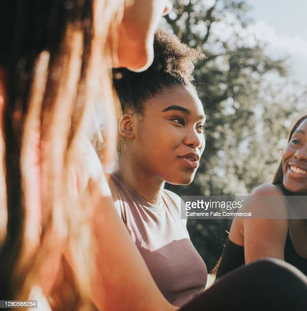 three girls in sportswear relax outside in the sun - determination stock pictures, royalty-free photos & images