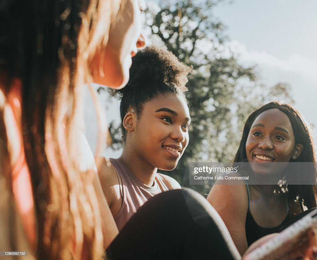 Three Girls in Sportswear relax outside in the Sun : Stock Photo