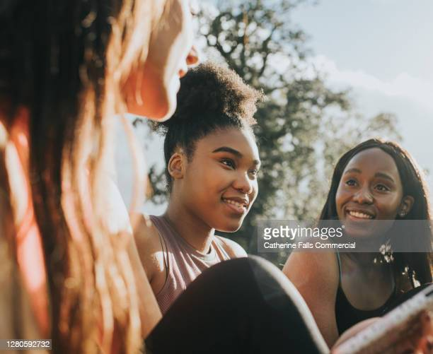 three girls in sportswear relax outside in the sun - listening stock pictures, royalty-free photos & images