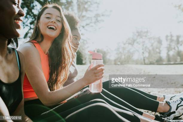 three girls in sportswear relax outside in the sun - sports stock pictures, royalty-free photos & images