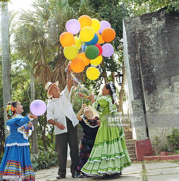 three girls (5-9) in traditional dress getting balloons from vendor - mexican fiesta stock pictures, royalty-free photos & images