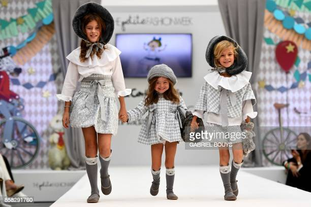 TOPSHOT Three girls including one with Down Syndrome present creations on the catwalk during 'The Petite Fashion Week' in Madrid on October 6 2017...