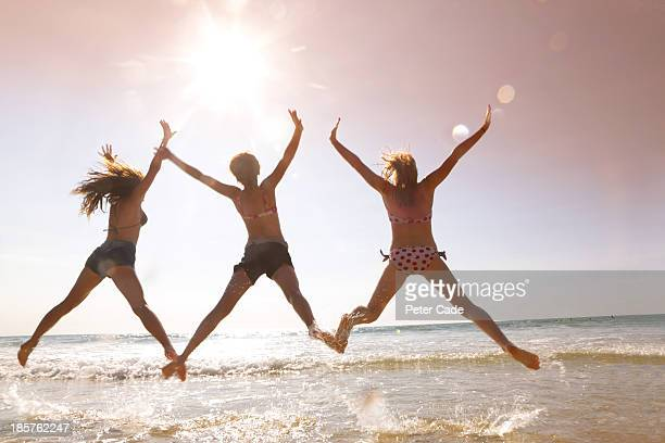 Three girls jumping in sea