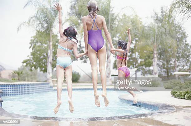 three girls jumping into a swimming pool - one piece swimsuit stock pictures, royalty-free photos & images