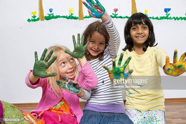 Three girls kneeling on floor with painted hands