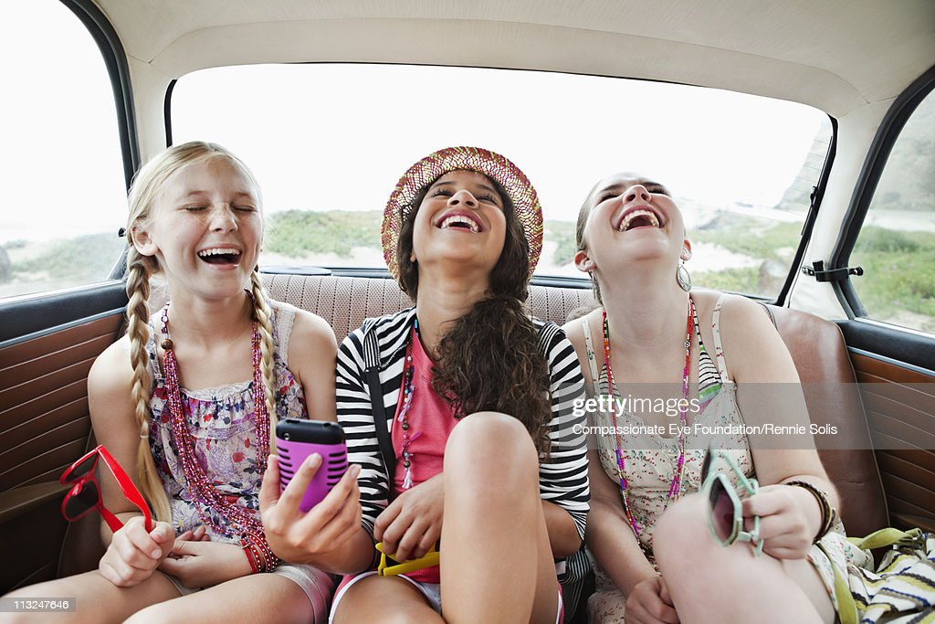 Three girls laughing in the back seat of a vehicle : Stock Photo
