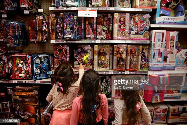 LOS Three girls look at shelves of dolls including Monster High and Ever After High dolls at Toys R Us on La Cienega Blvd Friday November 27 2015